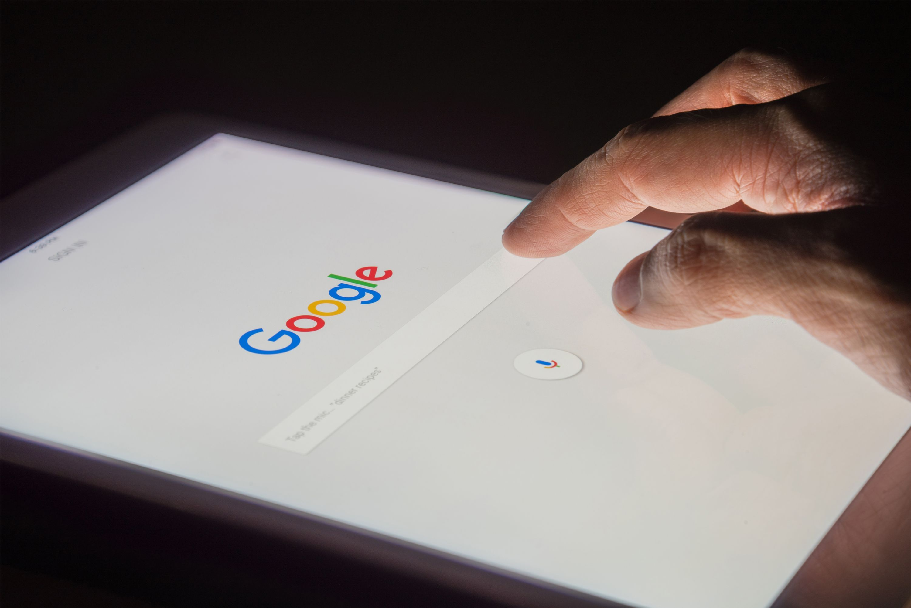A tablet showing Google homepage with a hand tapping on the search field.